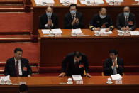 Chinese Premier Li Keqiang, center, bows after delivering a speech during the opening session of China's National People's Congress (NPC) at the Great Hall of the People in Beijing, Friday, March 5, 2021. (AP Photo/Andy Wong)