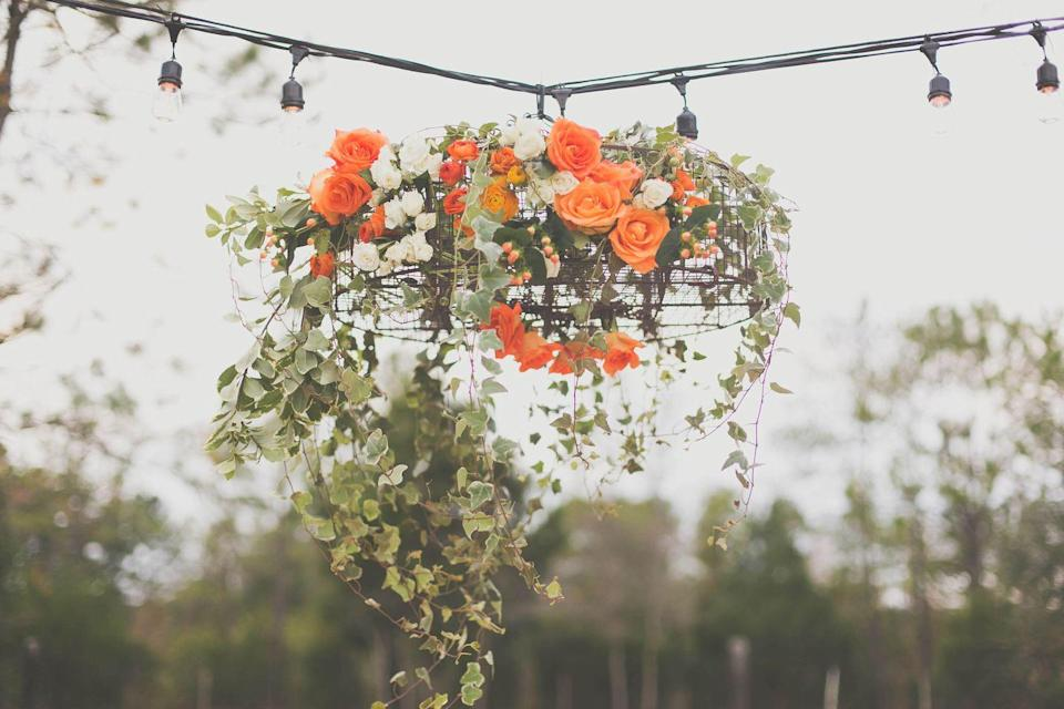 """<p>If you're planning an important outdoor autumn event, <a href=""""https://www.elledecor.com/shopping/g3457/best-modern-chandeliers/"""" rel=""""nofollow noopener"""" target=""""_blank"""" data-ylk=""""slk:consider a chandelier"""" class=""""link rapid-noclick-resp"""">consider a chandelier</a>, but swap the crystals for foliage and fall colors. In this gorgeous piece, <a href=""""http://emilyburtondesigns.com/flower-feature-friday-fall-floral-chandelier/"""" rel=""""nofollow noopener"""" target=""""_blank"""" data-ylk=""""slk:Emily Burton Designs"""" class=""""link rapid-noclick-resp"""">Emily Burton Designs</a> used large garden bulb lighting to frame a floral chandelier that served as a focal point for the table below. </p>"""