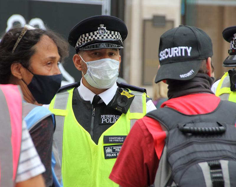 "Police officer wearing a face mask as he listens to a protester. A change in policy has meant that in some situations where social distancing is impossible, Police at demonstrations will wear Protective face masks. A spokesperson said: ""If officers cannot maintain a two metre gap and where there is a possible risk of infection, our policy is now that officers will wear a facemask, which all officers have readily available."" (Photo by Keith Mayhew / SOPA Images/Sipa USA)"