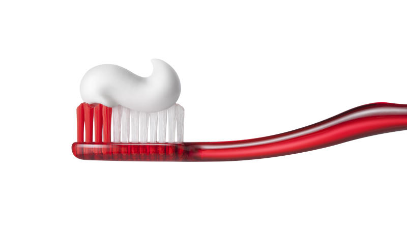 Toothbrush with toothpasteon on white background.