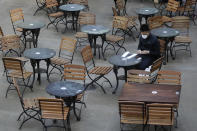 A man sits in an empty cafe in London, Thursday, Sept. 24, 2020, after Britain's Prime Minister Boris Johnson announced a range of new restrictions to combat the rise in coronavirus cases in England. (AP Photo/Kirsty Wigglesworth)