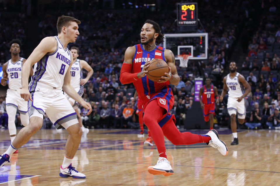 Detroit Pistons guard Derrick Rose, right, goes to the basket against Sacramento Kings guard Bogdan Bogdanovic during the first half of an NBA basketball game in Sacramento, Calif., Sunday, March 1, 2020. (AP Photo/Rich Pedroncelli)