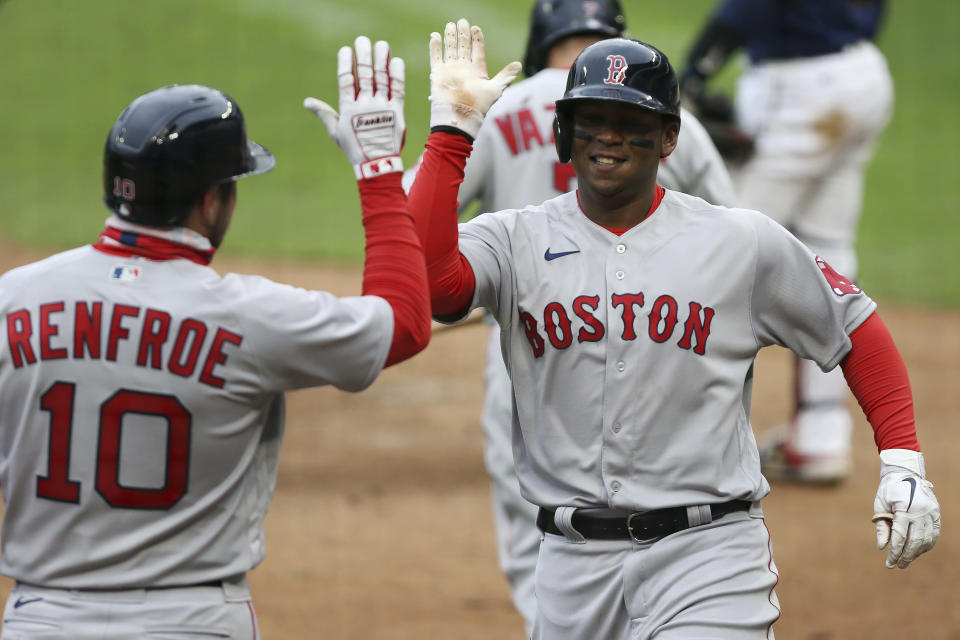 Boston Red Sox Rafael Devers (11) high fives teammate Boston Red Sox Hunter Renfroe (10) after hitting a home run against the Minnesota Twins during the ninth inning of a baseball game, Tuesday, April 13, 2021, in Minneapolis. Boston won 4-2. (AP Photo/Stacy Bengs)