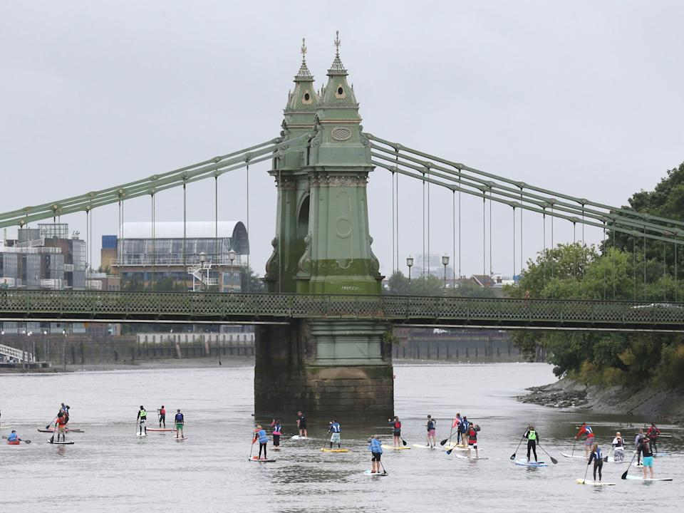 Paddle boarders approach Hammersmith bridge as they participate in the Laureus Stand up for good Thames Challenge on the river Thames in London