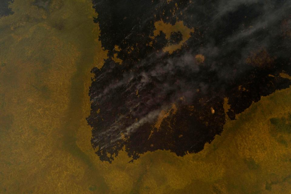 TOPSHOT - An aerial view shows smoke rising from fires in the wetlands of the Pantanal at the Transpantaneira park road in Mato Grosso state, Brazil, on September 14, 2020. - The Pantanal, a region famous for its wildlife, is suffering its worst fires in more than 47 years, destroying vast areas of vegetation and causing death of animals caught in the fire or smoke. (Photo by MAURO PIMENTEL / AFP) (Photo by MAURO PIMENTEL/AFP via Getty Images)