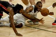 Miami Heat's Trevor Ariza and Milwaukee Bucks' Khris Middleton go after a loose ball during the first half of an NBA basketball game Saturday, May 15, 2021, in Milwaukee. (AP Photo/Morry Gash)