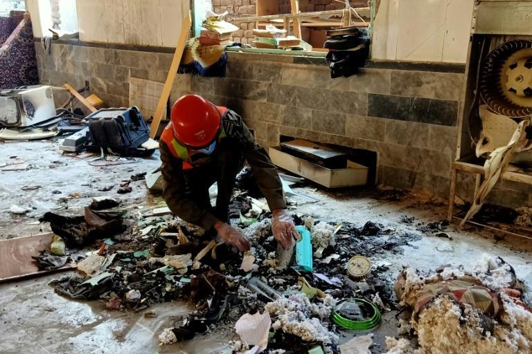 A rescue worker examines the scene of the blast at a religious school in Peshawar