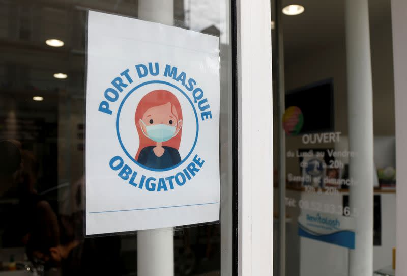 A sign asking customers to wear masks is seen at a shop in Vincennes