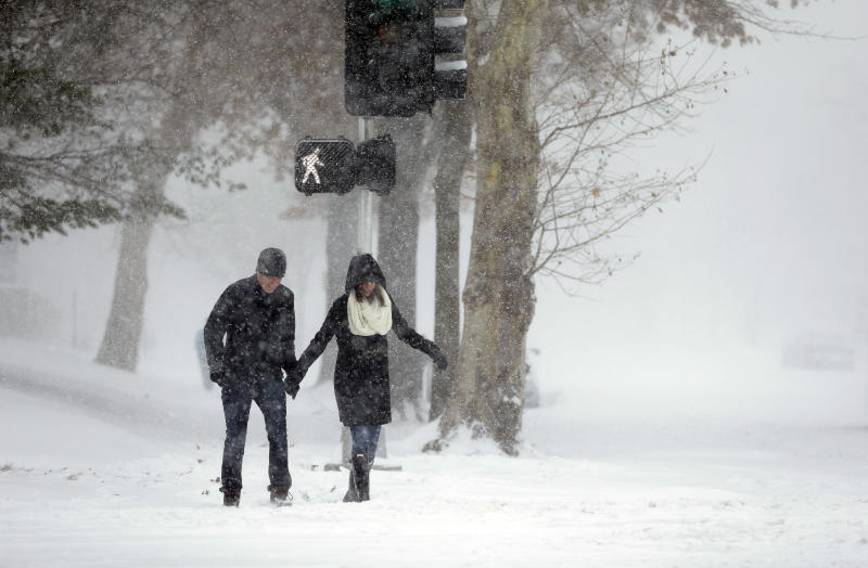 Andrew Loza, left, walks down a snow-covered sidewalk with Emily Olfson Sunday, Jan. 5, 2014, in St. Louis. Heavy snow continues to fall Sunday with forecasters calling for up to a foot (30 centimeters) in eastern Missouri and parts of central Illinois followed by bitter cold. (AP Photo/Jeff Roberson)