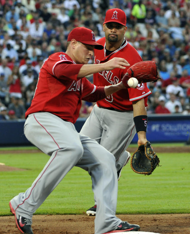 Los Angeles Angels pitcher Garrett Richards, left, is charged with a missed catch error from first baseman Albert Pujols, right, on a ground ball by Atlanta Braves' Jason Heyward during the third inning of a baseball game on Saturday, June 14, 2014, in Atlanta. (AP Photo/David Tulis)