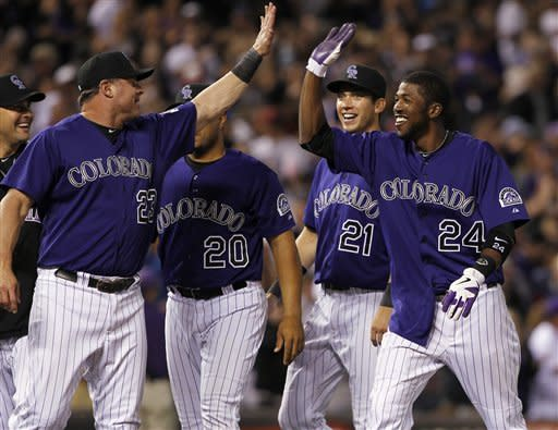 From right, Colorado Rockies' Dexter Fowler is congratulated by teammates Tyler Colvin, Wilin Rosario and Jason Giambi after Fowler's RBI-single to drive in the wining run against the Houston Astros in the 10th inning of the Rockies' 7-6 victory in in game two of a split doubleheader in Denver on Monday, May 28, 2012. (AP Photo/David Zalubowski)