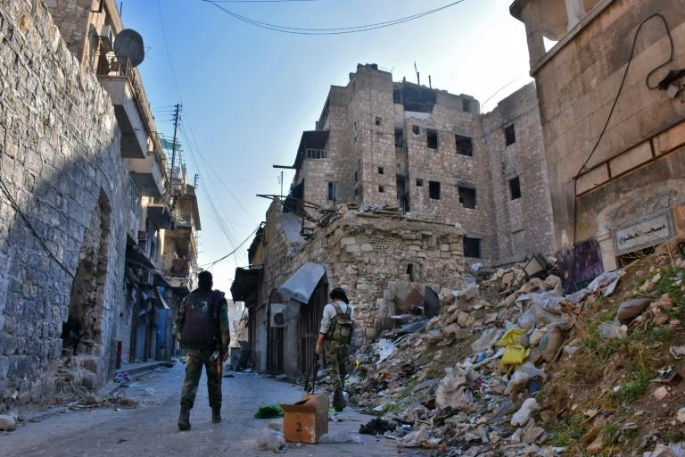 Syrian pro-government forces walk past rubble in old Aleppo on December 9, 2016