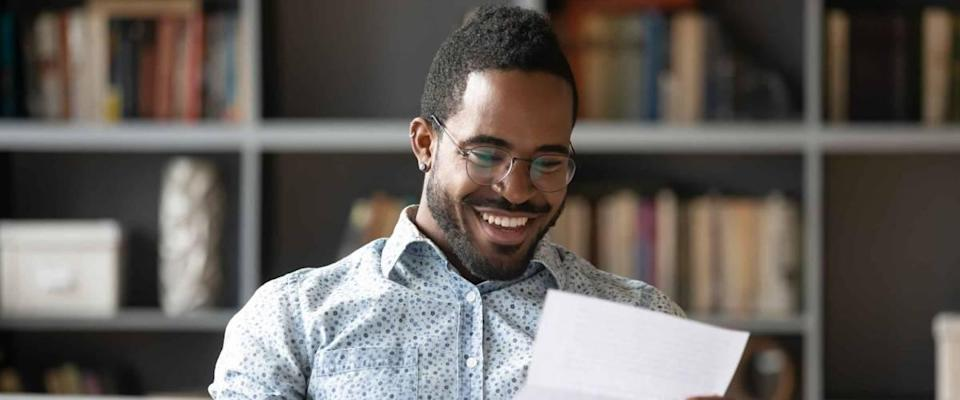 Happy smiling African American man wearing glasses reading letter.
