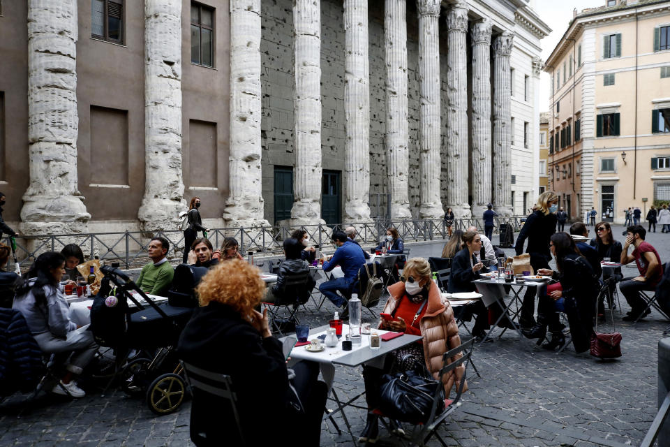 People eat in a restaurant in central Rome, Sunday, Oct. 25, 2020. For at least the next month, people outdoors except for small children must now wear masks in all of Italy, gyms, cinemas and movie theaters will be closed, ski slopes are off-limits to all but competitive skiers and cafes and restaurants must shut down in early evenings, under a decree signed on Sunday by Italian Premier Giuseppe Conte, who ruled against another severe lockdown despite a current surge in COVID-19 infections. (Cecilia FabianoLaPresse via AP)