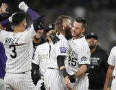 Colorado Rockies' C.J. Cron, right, is congratulated by Charlie Blackmon, center, and Dom Nunez after Cron drove in the winning run in the 10th inning of a baseball game against the Milwaukee Brewers on Friday, June 18, 2021, in Denver. The Rockies won 6-5. (AP Photo/David Zalubowski)