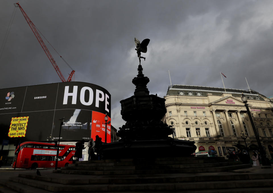 FILE - In this Friday, Jan. 29, 2021 file photo, the Anteros statue in Piccadilly Circus in London, above a sign saying HOPE on the advertising boards, during England's third national lockdown since the coronavirus outbreak began. Thanks to an efficient vaccine roll out program and high uptake rates, Britain is finally saying goodbye to months of tough lockdown restrictions. From Monday May 17, 2021, all restaurants and bars can fully reopen, as can hotels, cinemas, theatres and museums, and for the first time since March 2020, Britons can hug friends and family and meet up inside other people's houses. (AP Photo/Kirsty Wigglesworth, File)