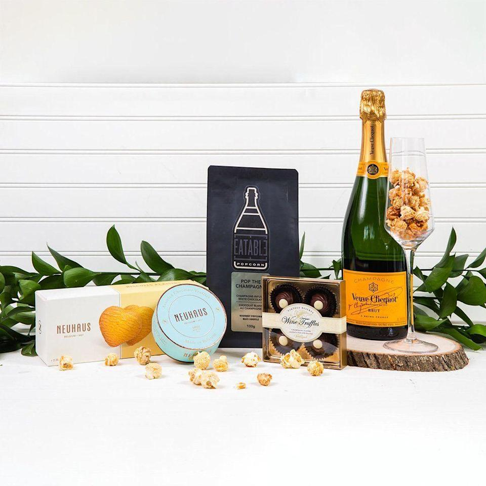 """<p><strong>GiftBasket.com</strong></p><p>giftbasket.com</p><p><strong>$159.99</strong></p><p><a href=""""https://go.redirectingat.com?id=74968X1596630&url=https%3A%2F%2Fgiftbasket.com%2Fproducts%2Fpop-the-champagne%3Fvariant%3D31971816570978%26gclid%3DCj0KCQjwqKuKBhCxARIsACf4XuHD01Fap-V7MTijAHaaEixA8O92M1ZhShJUcI3ecjL1aIa6HUE6NuQaArtiEALw_wcB&sref=https%3A%2F%2Fwww.cosmopolitan.com%2Flifestyle%2Fg37682336%2Fbest-wine-gift-baskets%2F"""" rel=""""nofollow noopener"""" target=""""_blank"""" data-ylk=""""slk:Shop Now"""" class=""""link rapid-noclick-resp"""">Shop Now</a></p><p>ICYMI, there's a popping theme here. This beaut comes with a bottle of Veuve Clicquot, champagne-infused popcorn (I know), truffles, and expensive cookies. </p>"""