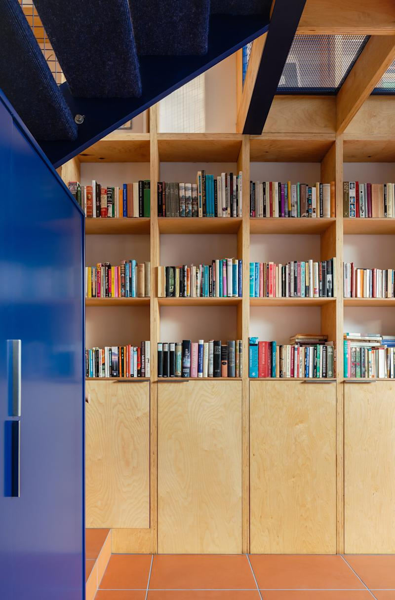 The owner's collection of books is stored in a bookcase that spans two levels. The ground level has the kitchen and dining areas; then there's a half-level with an original dining room, and finally the second level with a study and reading nook.