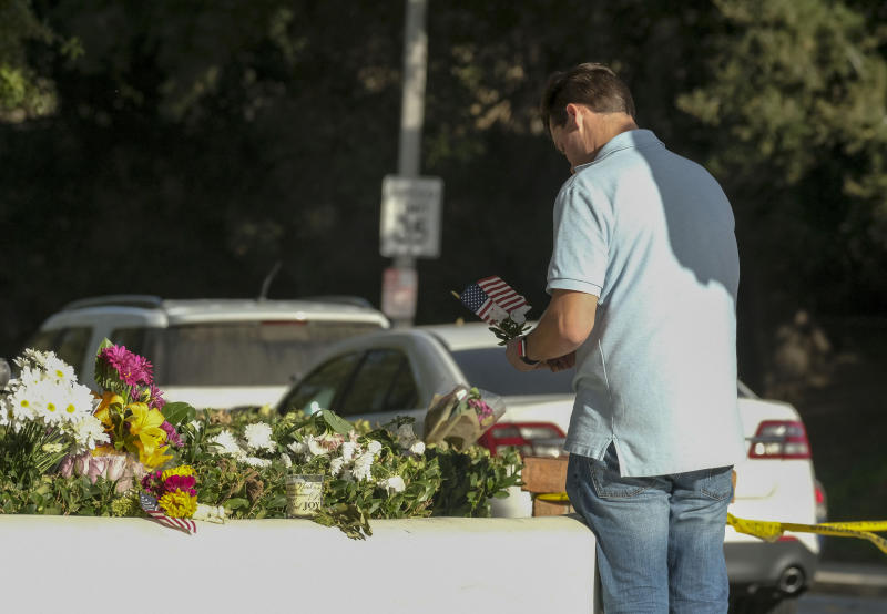 Brian White places a U.S. flag with a flower near the scene of a mass shooting Thursday, Nov. 8, 2018, in Thousand Oaks, Calif., after a gunman opened fire Wednesday evening inside a country music bar, killing multiple people including a responding sheriff's sergeant. (AP Photo/Ringo H.W. Chiu)