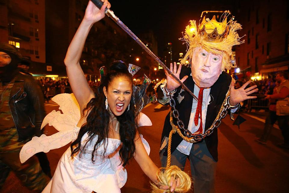 <p>Marni Halasa brandishes a sword in front of a man in a Donald Trump costume with a sword at the 44th annual Village Halloween Parade in New York City on Oct. 31, 2017. (Photo: Gordon Donovan/Yahoo News) </p>