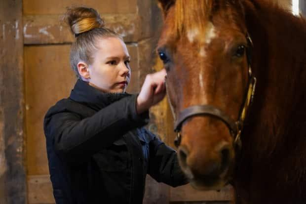 Fourteen-year-old Gracie brushes CeeLo. Gracie is frank about how working with horses helped her get through a very difficult time in her life.