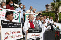 "Medical workers wear face masks and hold placards while staging a sit-in protest at the Unknown Soldier Square in Gaza City, Wednesday, Oct. 21, 2020. Arabic reads ""Makassed hospital is a national address for the Palestinian people."" ""We call on President Abu Mazen to intervene and bring us back to work."" Seven medical workers from the Gaza Strip said Wednesday an Israeli travel ban deprived them from getting to the east Jerusalem hospital where they worked for many years and the hospital eventually fired them. (AP Photo/Adel Hana)"