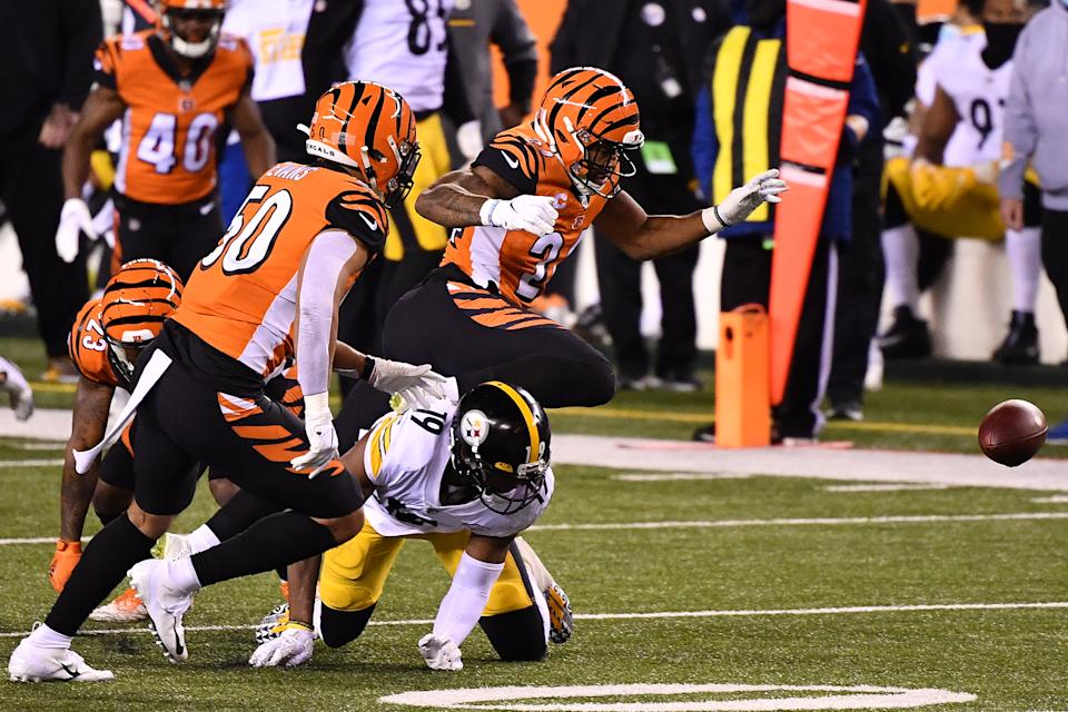 CINCINNATI, OHIO - DECEMBER 21: Vonn Bell #24 of the Cincinnati Bengals forces a fumble by JuJu Smith-Schuster #19 of the Pittsburgh Steelers during the first quarter at Paul Brown Stadium on December 21, 2020 in Cincinnati, Ohio. (Photo by Jamie Sabau/Getty Images)