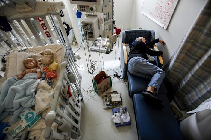 Jeff Catania, 60, falls asleep next to his two-month-old son Dylan in a hospital room