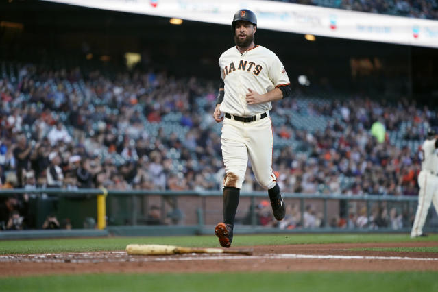 San Francisco Giants' Brandon Belt scores a run on a single by Stephen Vogt during the first inning against the Arizona Diamondbacks in a baseball game in San Francisco, Tuesday, Aug. 27, 2019. (AP Photo/Tony Avelar)
