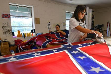 Cynthia Hernandez places stars on a Confederate Battle Flag in the Alabama Flag & Banner shop in Huntsville, Alabama, U.S., August 24, 2017. REUTERS/Harrison McClary