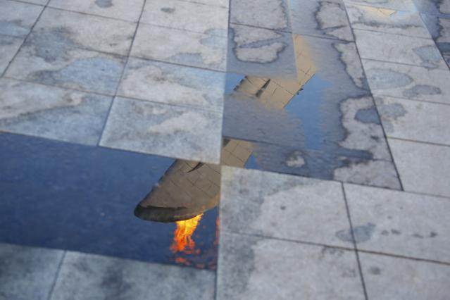 The Olympic flame is reflected in a puddle at the Olympic Park during the 2014 Sochi Winter Olympics, February 21, 2014. REUTERS/Eric Gaillard (RUSSIA - Tags: OLYMPICS SPORT TPX IMAGES OF THE DAY)