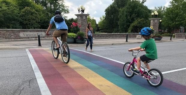 People ride bikes near Victoria Park in downtown Kitchener, the heart of the Kitchener Centre riding. Polls indicate the federal election race in the riding is a close one between the Conservative, Green Party and NDP candidates. (Kate Bueckert/CBC - image credit)