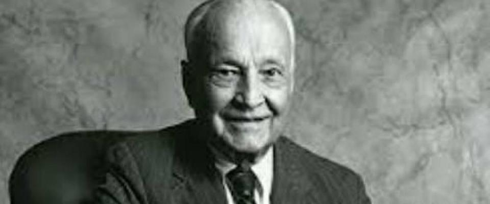 Sir John Templeton poses for the camera, sitting at a desk, smiling.