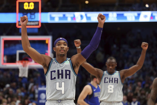 Charlotte Hornets guard Devonte' Graham (4) and center Bismack Biyombo (8) react after a win over the Dallas Mavericks in overtime in an NBA basketball game Saturday, Jan. 4, 2020, in Dallas. (AP Photo/Richard W. Rodriguez)