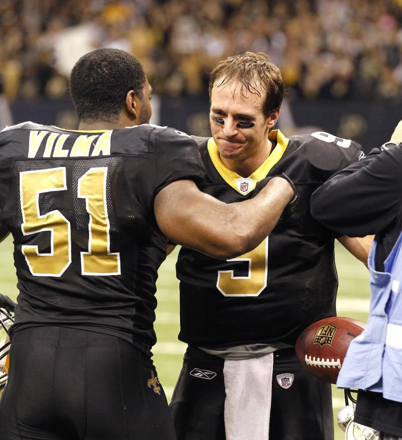 FILE - In this Dec. 26, 2011, file photo, New Orleans Saints quarterback Drew Brees (9) celebrates with linebacker Jonathan Vilma (51) after breaking Dan Marino's all-time season passing record in the fourth quarter of an NFL football game against the Atlanta Falcons in New Orleans. Brees defended Vilma in a court document filed Saturday, july 21, 2012, to support Vilma's fight against the NFL over his season-long suspension.  The affidavit was entered in New Orleans federal court as evidence for Vilma's motion to dismiss the 2012 suspension imposed by NFL Commissioner Roger Goodell, for the linebacker's alleged involvement in a program offering bonuses to players who injure opponents.  (AP Photo/Bill Haber, File)