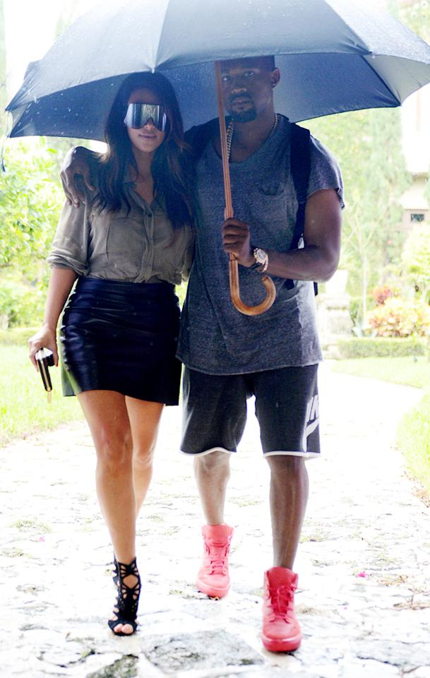 A rainy day couldn't keep the attention-grabbing couple from looking fashionable. Kim sported a pair of $750 Rick Owens shades while Yeezy put his best foot forward in a pair of red kicks. (10/8/12)