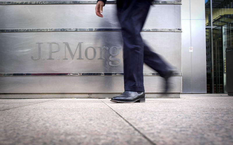 FILE - In this Aug. 8, 2012, file photo, a banker walks past JPMorgan Chase offices in London.  JPMorgan Chase, the country's biggest bank by assets, reported a record quarterly profit Friday, Oct. 12, 2012. The bank said it made $5.3 billion in earnings for common shareholders, a widely used measurement, from July through September, up 36 percent from the same period a year ago.(AP Photo/dapd,Timur Emek)