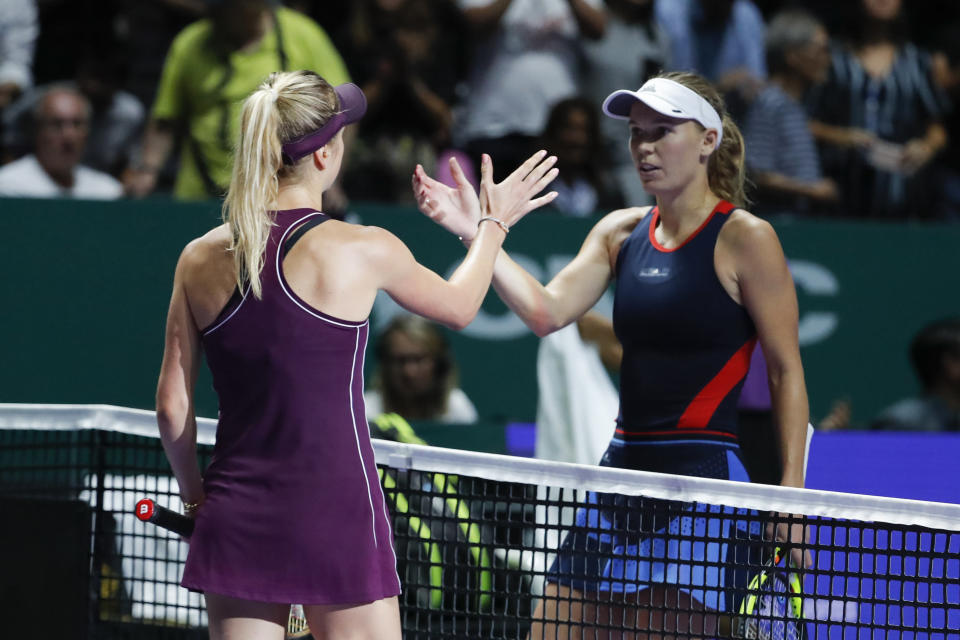 Elina Svitolina of the Ukraine, left, greets by Caroline Wozniacki of Denmark after their women's singles match at the WTA tennis finals in Singapore, Thursday, Oct. 25, 2018. (AP Photo/Vincent Thian)