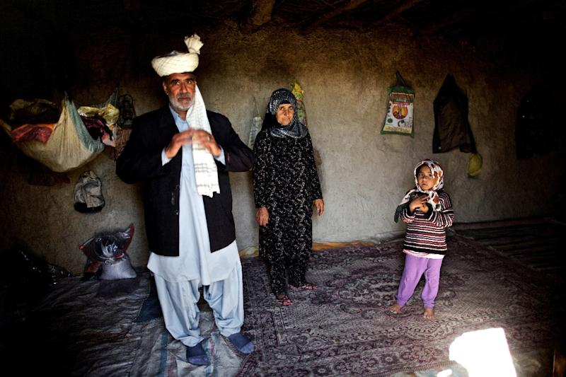 Iranian Annazar Sarani poses with his family inside their one-room mud house in the village of Sikhsar, where wooden boats sit on hard mud that was once the waterfront (AFP Photo/Behrouz Mehri)