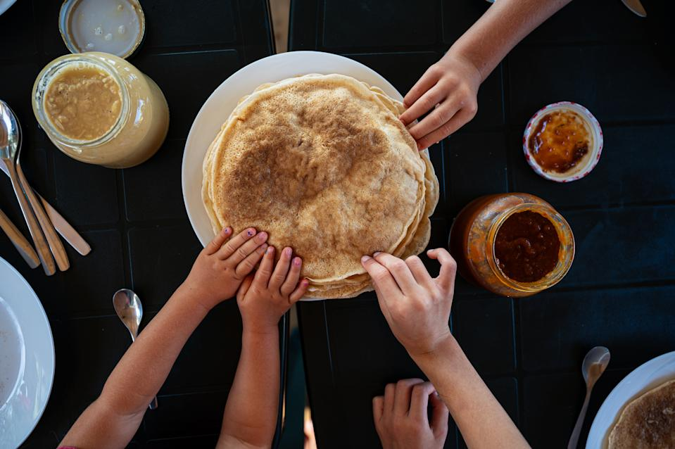 Top view of kids reaching for crepes at a breakfast table.