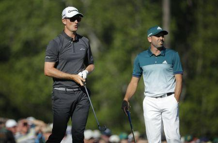 Justin Rose of England (L) watches his tee shot on the 12th with Sergio Garcia of Spain in final round play during the 2017 Masters golf tournament at Augusta National Golf Club in Augusta, Georgia, U.S., April 9, 2017. REUTERS/Mike Segar