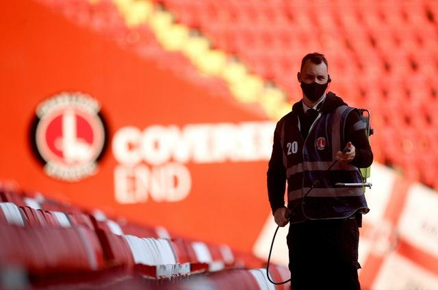 A steward disinfects the seats after the game at The Valley