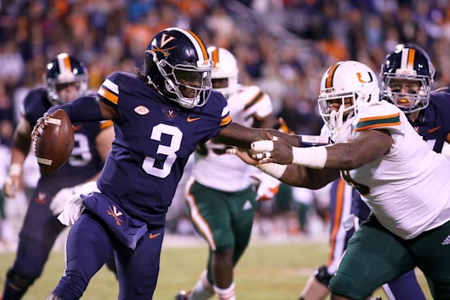 """Virginia's Bryce Perkins stiff-arms Miami's <a class=""""link rapid-noclick-resp"""" href=""""/ncaaf/players/240107/"""" data-ylk=""""slk:Gerald Willis III"""">Gerald Willis III</a> in the first half the Hurricanes' loss to the Cavaliers. (AP)"""
