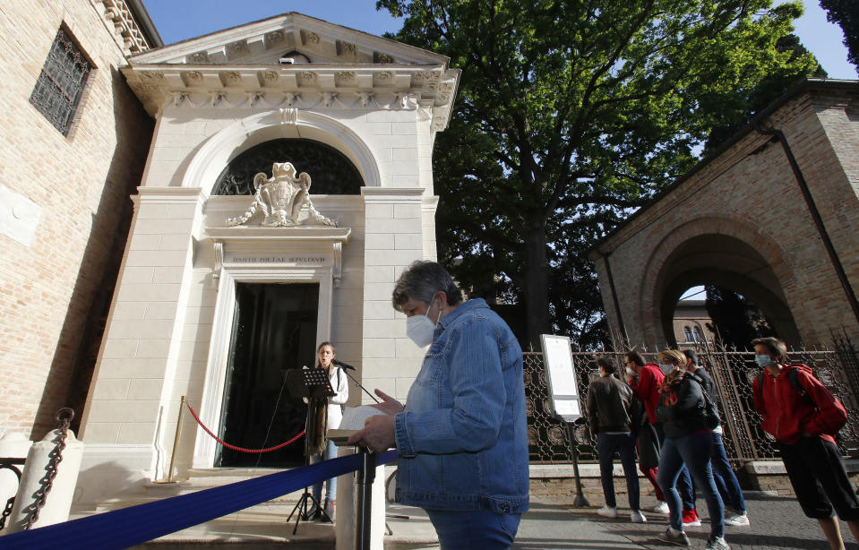"""Ravenna citizen Giuliana Turati, center, holds a copy of poet Dante Alighieri's Divina Commedia """"Divine Comedy"""" as she listens to a reading by volunteer Carlotta Zangolli in front of Dante's tomb, in Ravenna, Italy, Saturday, May 8, 2021. Italy is honoring its great poet in myriad ways on the 700th anniversary of his death, with new musical scores and gala concerts, exhibits and dramatic readings against stunning backgrounds in every corner of the land. (AP Photo/Antonio Calanni)"""