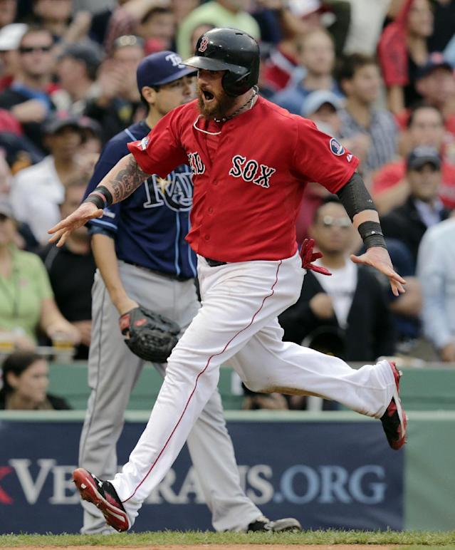 Boston Red Sox's Jonny Gomes scores on a double by Jarrod Saltalamacchia in the fifth inning in Game 1 of baseball's American League division series against the Tampa Bay Rays, Friday, Oct. 4, 2013, in Boston. (AP Photo/Charles Krupa)