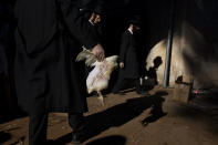 An Ultra-Orthodox Jewish man holds a chicken during the Kaparot ritual in Bnei Brak, Israel, Tuesday, Sept. 14, 2021. Observant Jews believe the ritual transfers one's sins from the past year into the chicken, and is performed before the Day of Atonement, Yom Kippur, the holiest day in the Jewish year which starts at sundown Wednesday. (AP Photo/Oded Balilty)