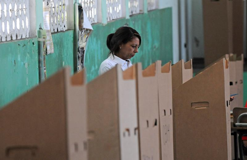 A woman mark her ballot during the presidential election in Santo Domingo, Dominican Republic, Sunday May 20, 2012. (AP Photo/Manuel Diaz)
