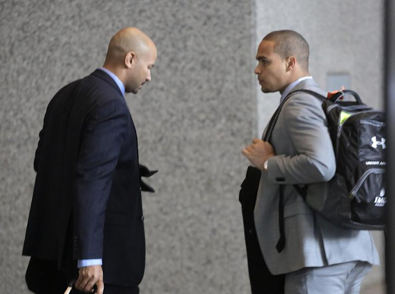 College Athletes Players Association designated president Ramogi Huma, left, and Northwestern University outgoing senior quarterback Kain Colter make their way to the beginning of three days of hearings before the National Labor Relations Board Tuesday, Feb. 18, 2014, in Chicago. The NLRB is scheduled to begin witness testimony on whether to approve a bid by Northwestern University football players who are trying to unionize.Colter is among the key witnesses in the case. (AP Photo/M. Spencer Green)