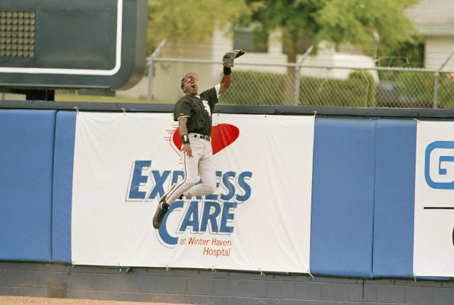 Michael Jordan leaps high against the outfield wall for a ball, in an exhibition game in Winter Haven, FL., March 10, 1994. (AP Photo/Charles Krupa)