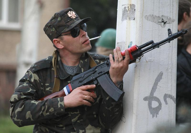 A pro-Russian gunman prepares his weapon as his comrades are about to storm a regional police station building in Luhansk, Ukraine, one of the largest cities in Ukraine's troubled east, Tuesday, April 29, 2014, as demonstrators demand greater autonomy for Ukraine's regions. The action on Tuesday further raises tensions in the east, where insurgents have seized control of police stations and other government buildings in at least 10 cities and towns. (AP Photo)